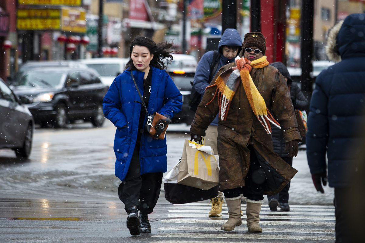 People walking through Chinatown, near West Cermak and South Wentworth, brave snowfall and temperatures that plummeted to the teens, Thursday morning, Feb. 13, 2020.