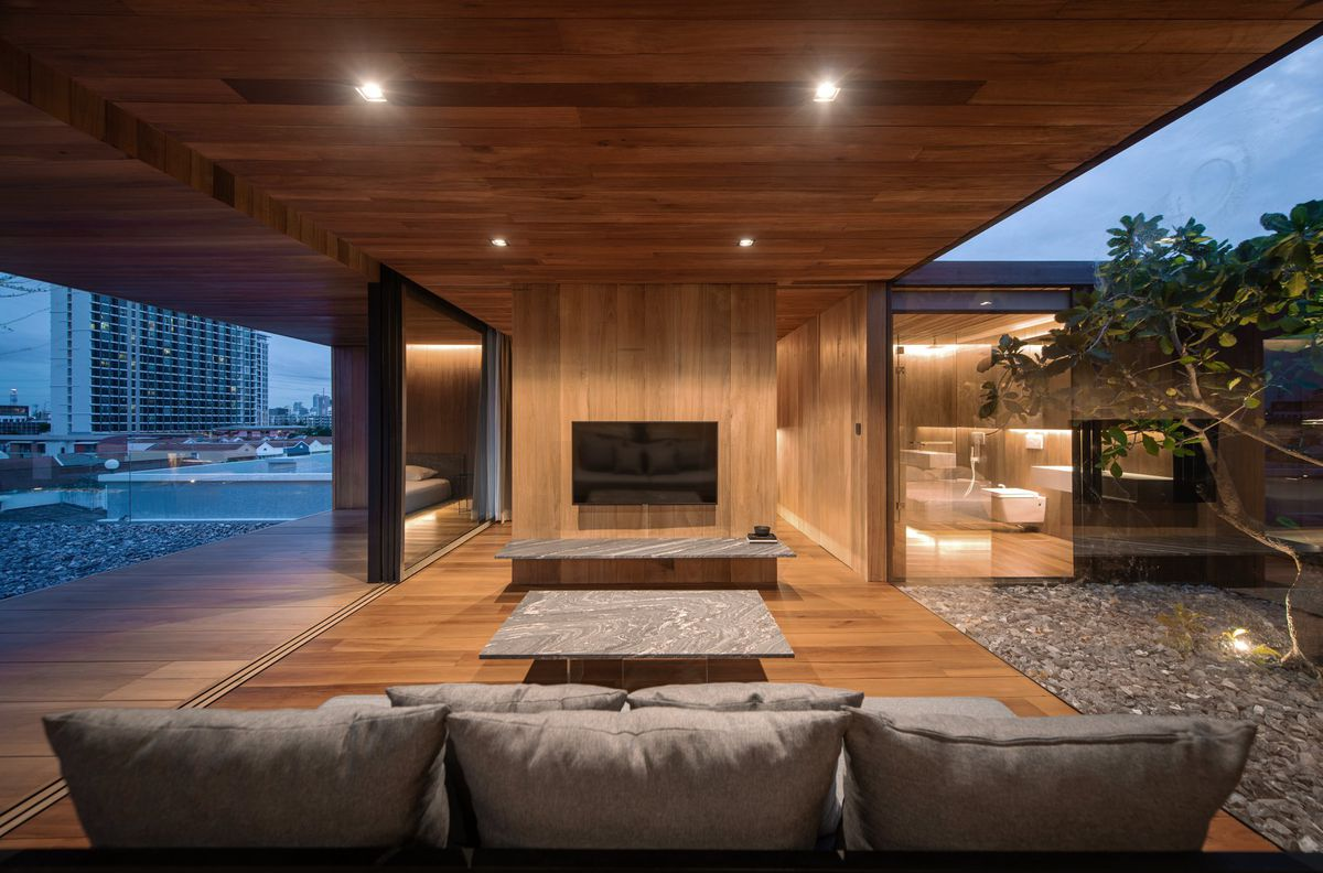 Living room surrounded by glass walls that have been opened to the outside.