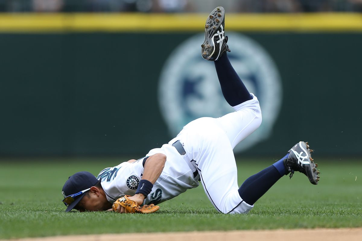 SEATTLE, WA - AUGUST 19:  Munenori Kawasaki #61 of the Seattle Mariners face plants after diving for a single by Justin Morneau of the Minnesota Twins at Safeco Field on August 19, 2012 in Seattle, Washington.  (Photo by Otto Greule Jr/Getty Images)