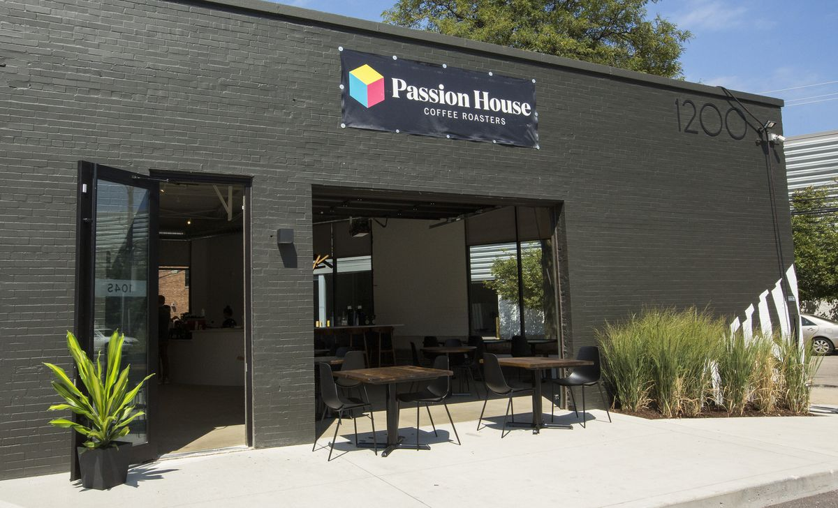 """Black brick coffee shop with """"1200"""" address in right upper corner with doors and windows open, plus green bushes."""