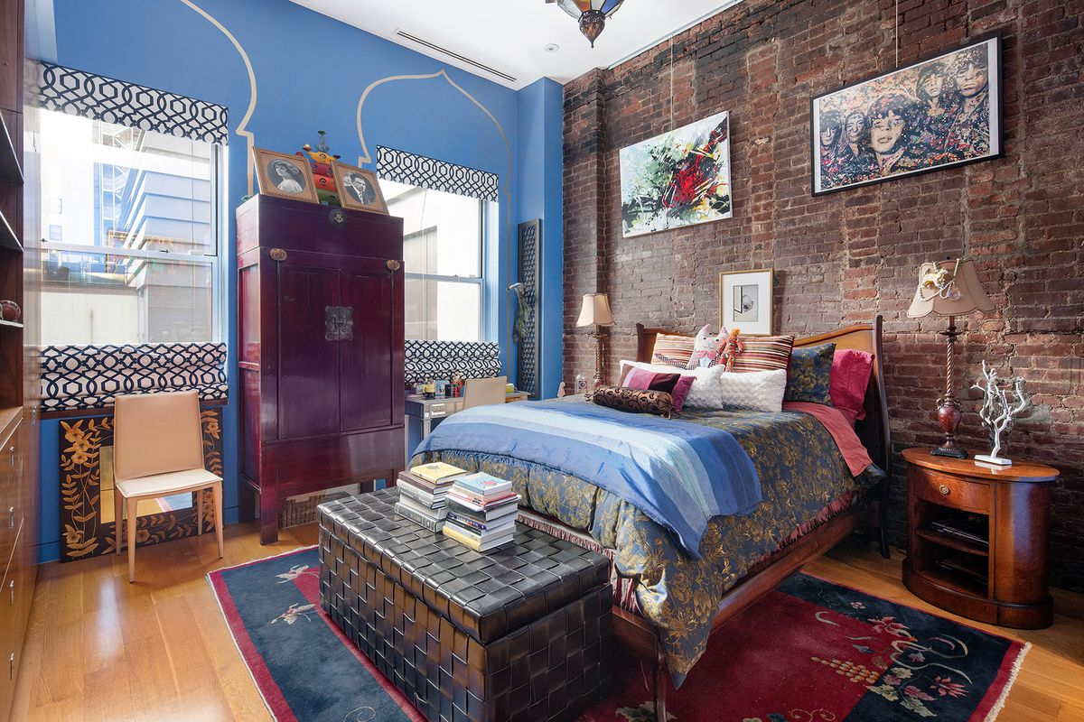 A bedroom with a medium-sized bed, exposed brick, two windows, blue walls, hardwood floors, and a rug.