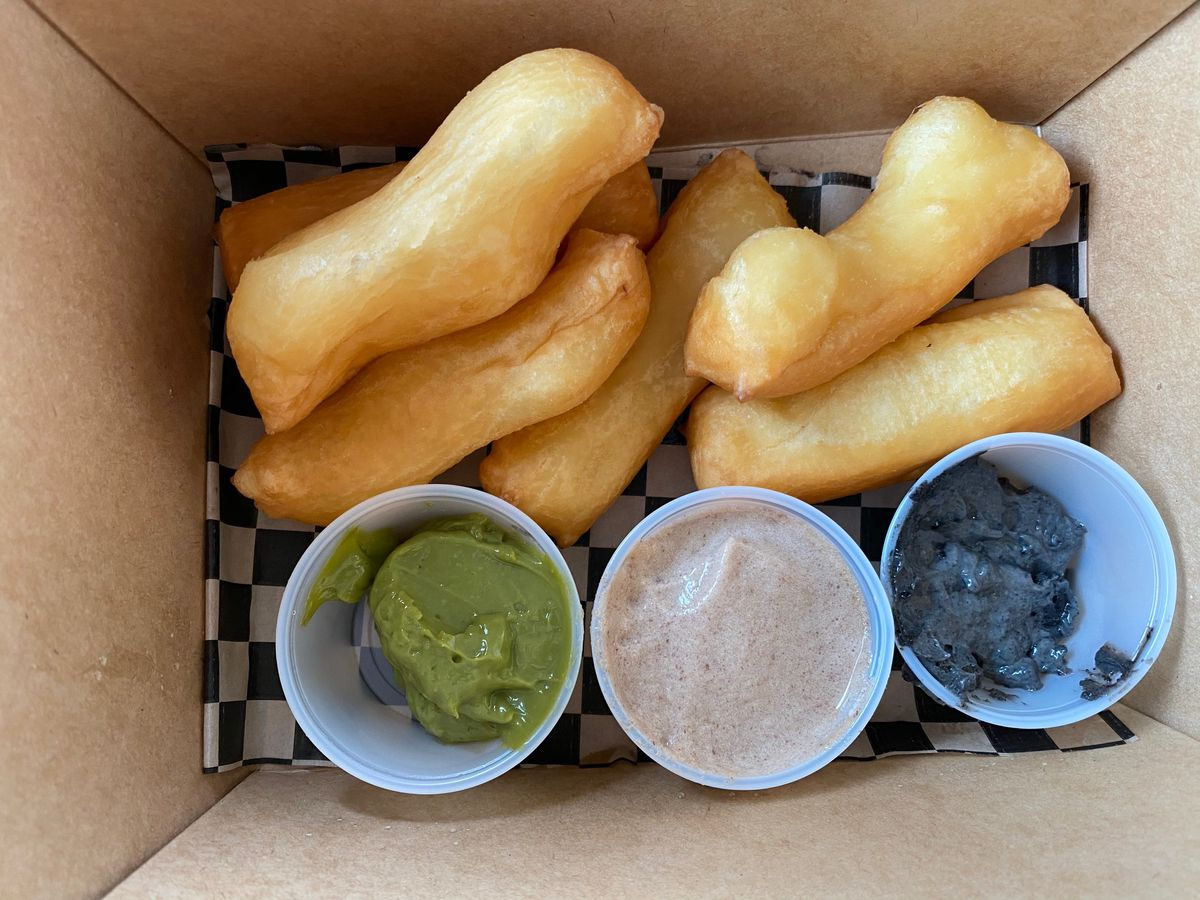 Takeout container of oblong mochi doughnuts, with three dipping sauces