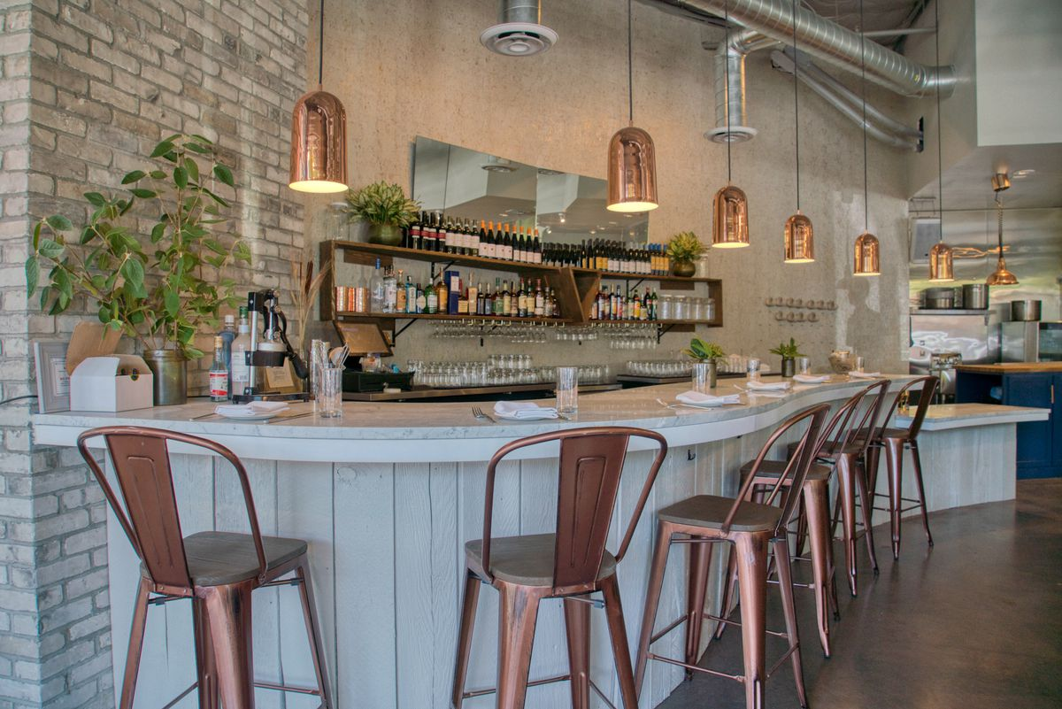 The bar seating at Haymaker with light brick walls and copper chairs.