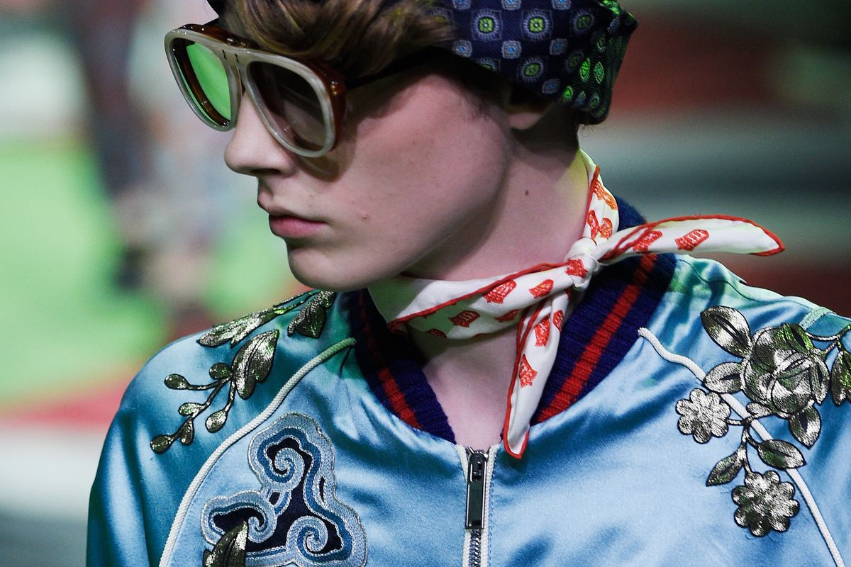 """A model walks the runway at Gucci's menswear show in Milan on Monday, wearing a baby blue silk bomber embroidered with an """"M."""""""