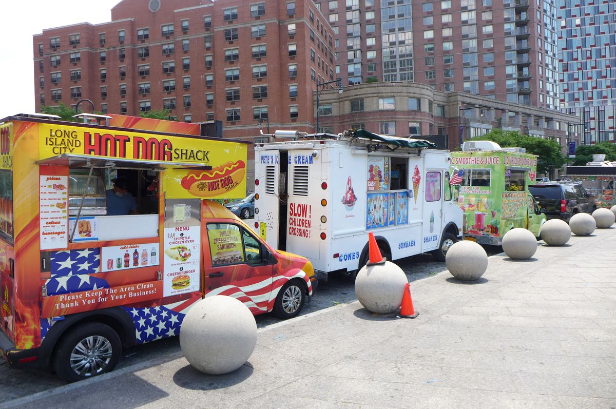 Three food trucks with condos in the background.