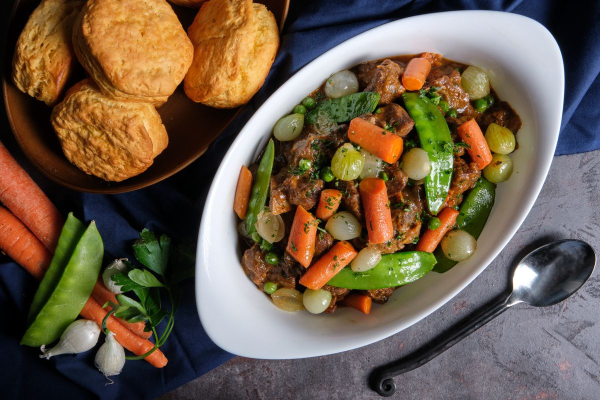 Lamb and vegetable stew in a white dutch oven