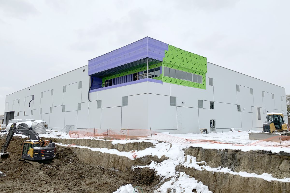 A gray, rectangular building with purple and green accents and square windows. Dirt is being excavated around the perimeter.