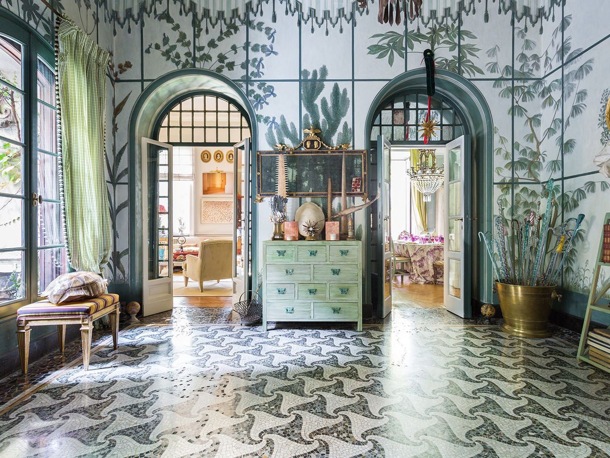 The interior of Casa Degli Atellani in Milan. The walls and floor are patterned. There are arched doorways and a tall window.
