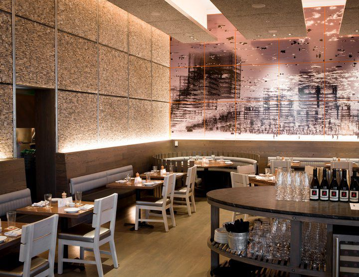A restaurant with tones of silver, gray, and brown has backlit bench seating with tables and low chairs