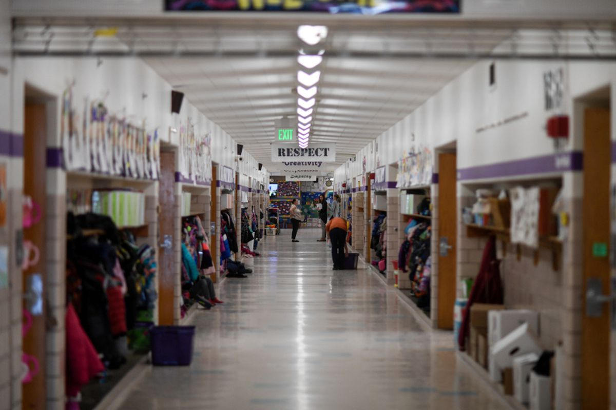 """An elementary school hallway with jackets on hooks and lunch bags on shelves, with two adults in the distance. Banners, one saying """"Respect,"""" hang from the ceiling between lights."""