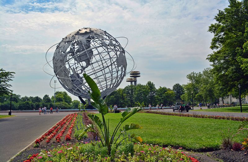 A park. In the foreground is a lawn with a garden. In the distance is a metallic spherical sculpture of the Earth. The sculpture is surrounded by trees.