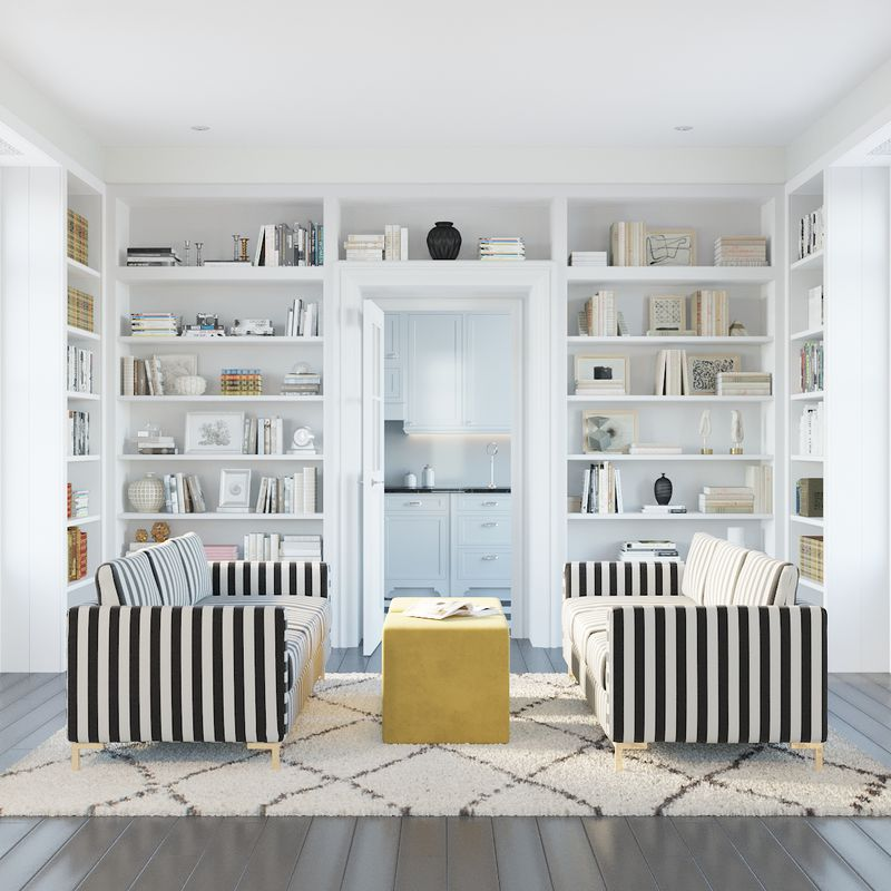 Two black-and-white striped sofas facing each other. An all-white built-in bookshelf in the background.