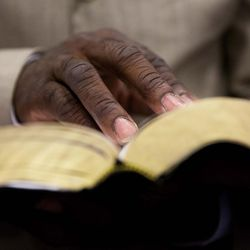 Ladine Daniels Sr. reads from a bible during a service at Charity Missionary Baptist Church in the wake of the death of Walter Scott, the black driver who was fatally shot by a white police officer after he fled a traffic stop, Sunday, April 12, 2015, in North Charleston, S.C. The officer, Michael Thomas Slager, has been fired and charged with murder.