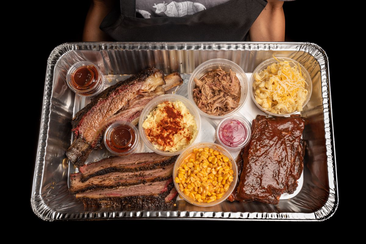 An overhead shot of a tin of barbecue with brisket, ribs, sides, and more.