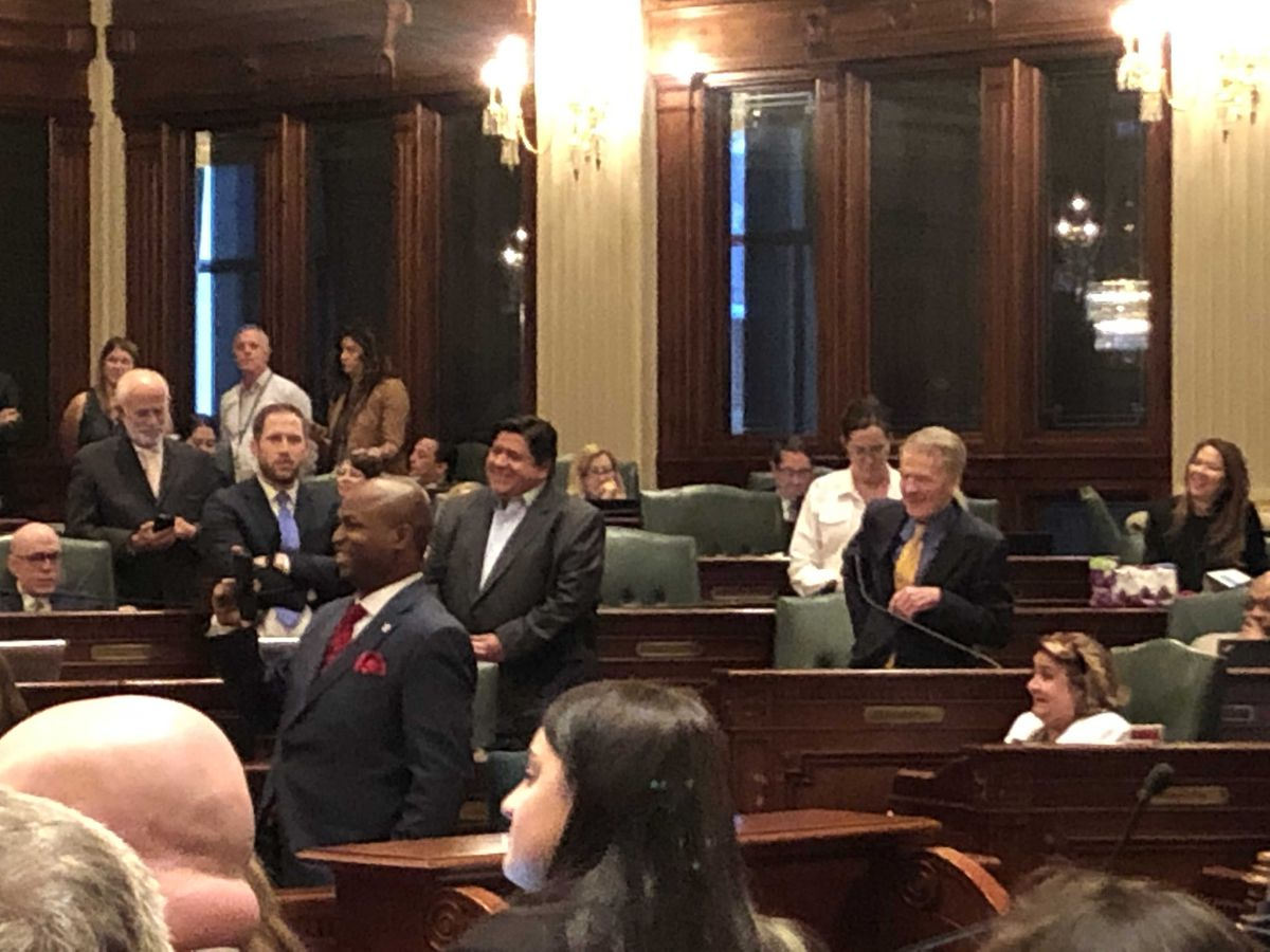 Gov. J.B. Pritzker and House Speaker Michael Madigan celebrate Saturday on the floor of the statehouse in Springfield after the House passed the state's first major capital plan since 2009.