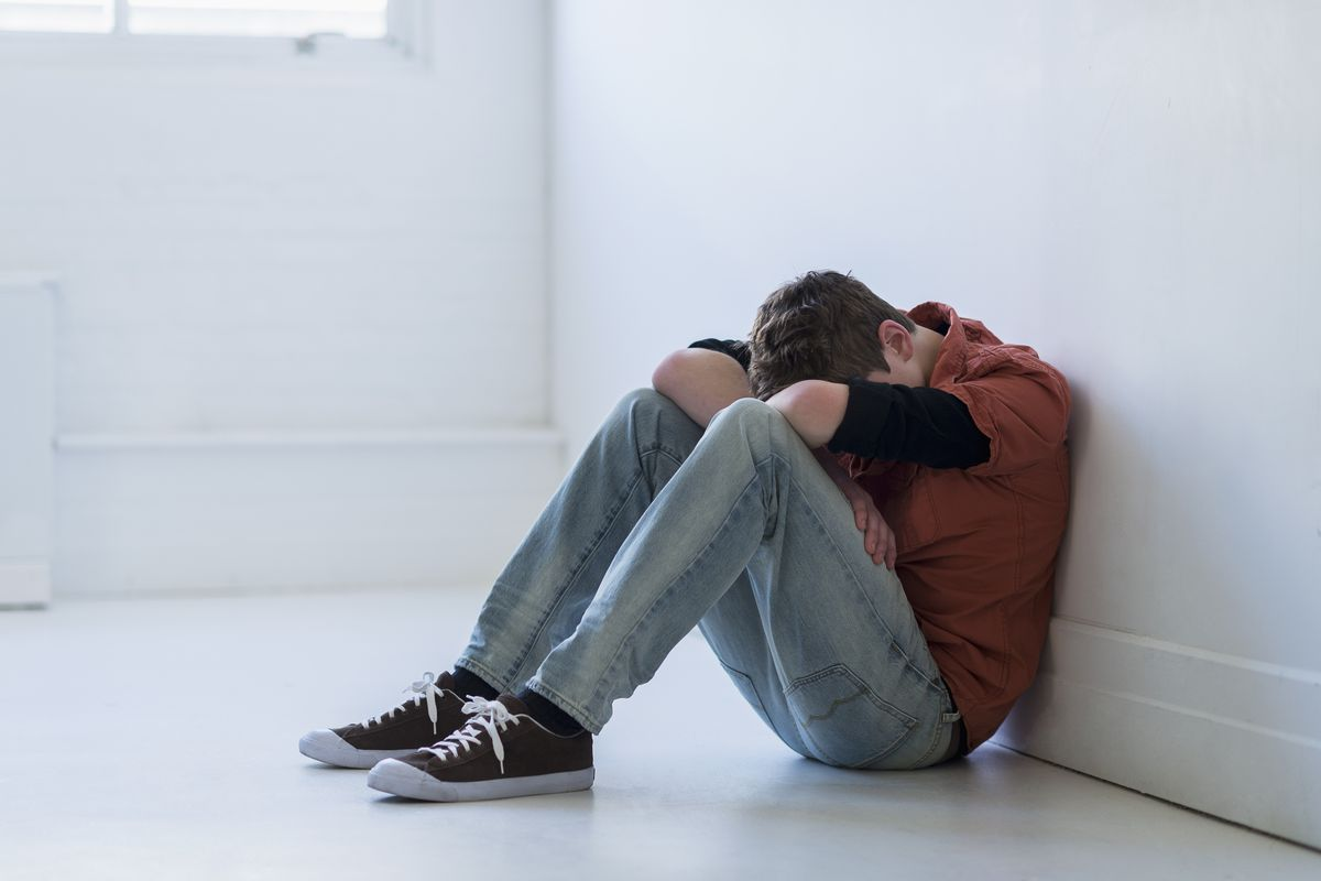 Teenage boy sitting in hallway. (Tetra Images   Getty Images)