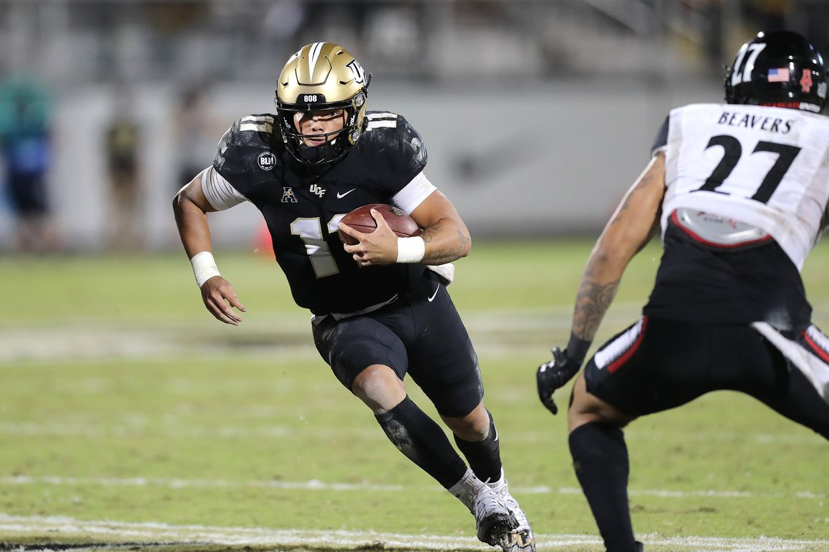 Dillon Gabriel of the Central Florida Knights scrambles against Darrian Beavers of the Cincinnati Bearcats at Bounce House-FBC Mortgage Field on November 21, 2020 in Orlando, Florida.