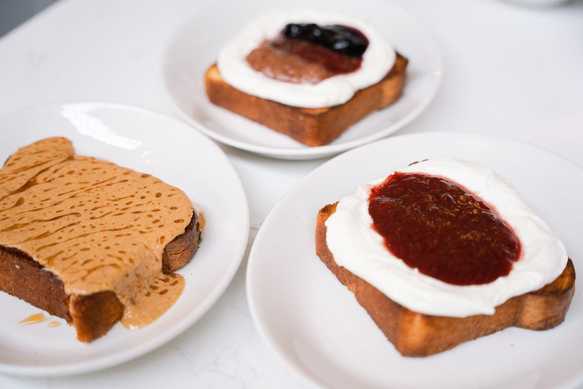 Three toasts sit on white plates; the one to the far left has nut butter, the one to the right has red jam and ricotta; and the one in the back has a mix of different jams with ricotta.