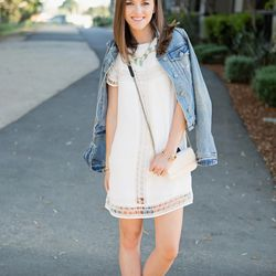 Caroline Rooney's toughens up a sweet white dress with a denim jacket and brown suede booties.