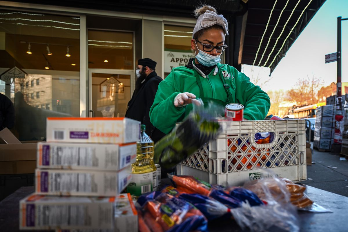 Masbia food pantry worker Carolina Sanchez restocks food at their outside pick-up tables.