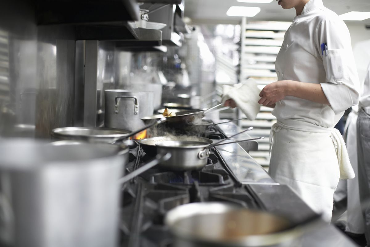 A female chef, dressed in white and visible from the chin down, stands over the stove in a restaurant kitchen