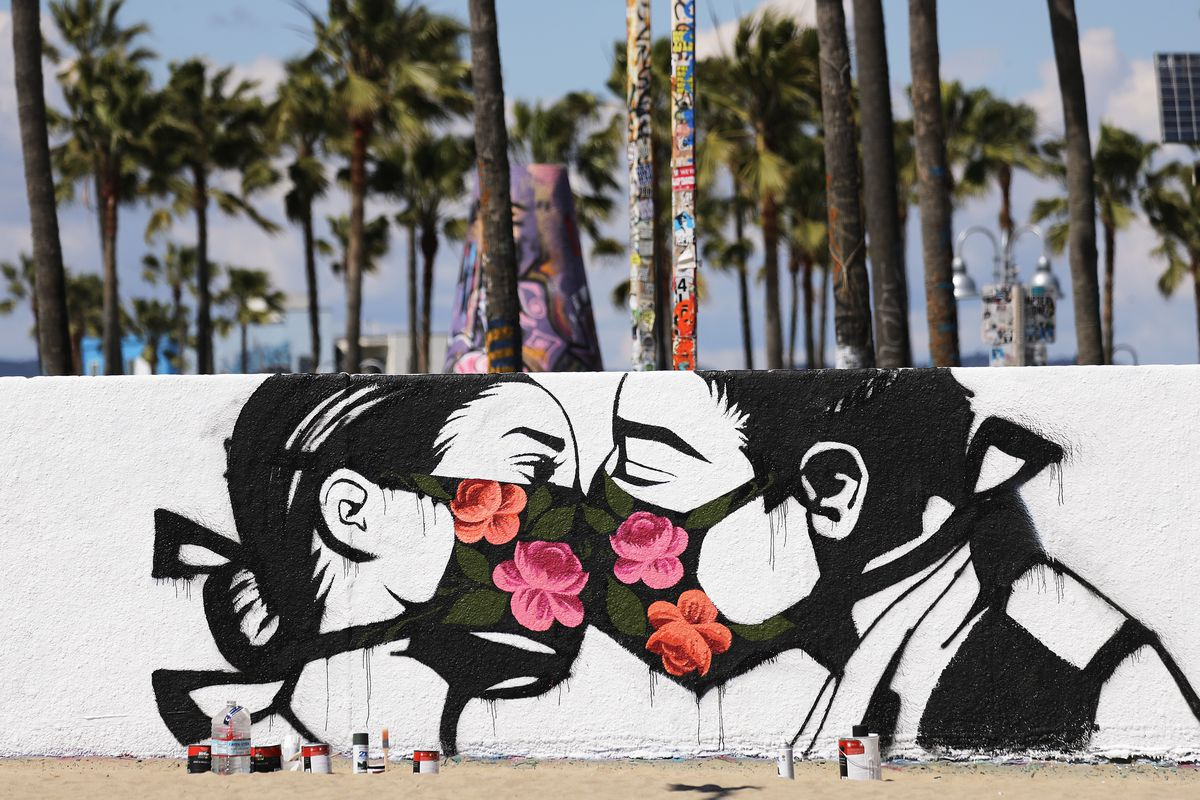 A mural depicts two people kissing while wearing face masks on Venice Beach in Los Angeles.
