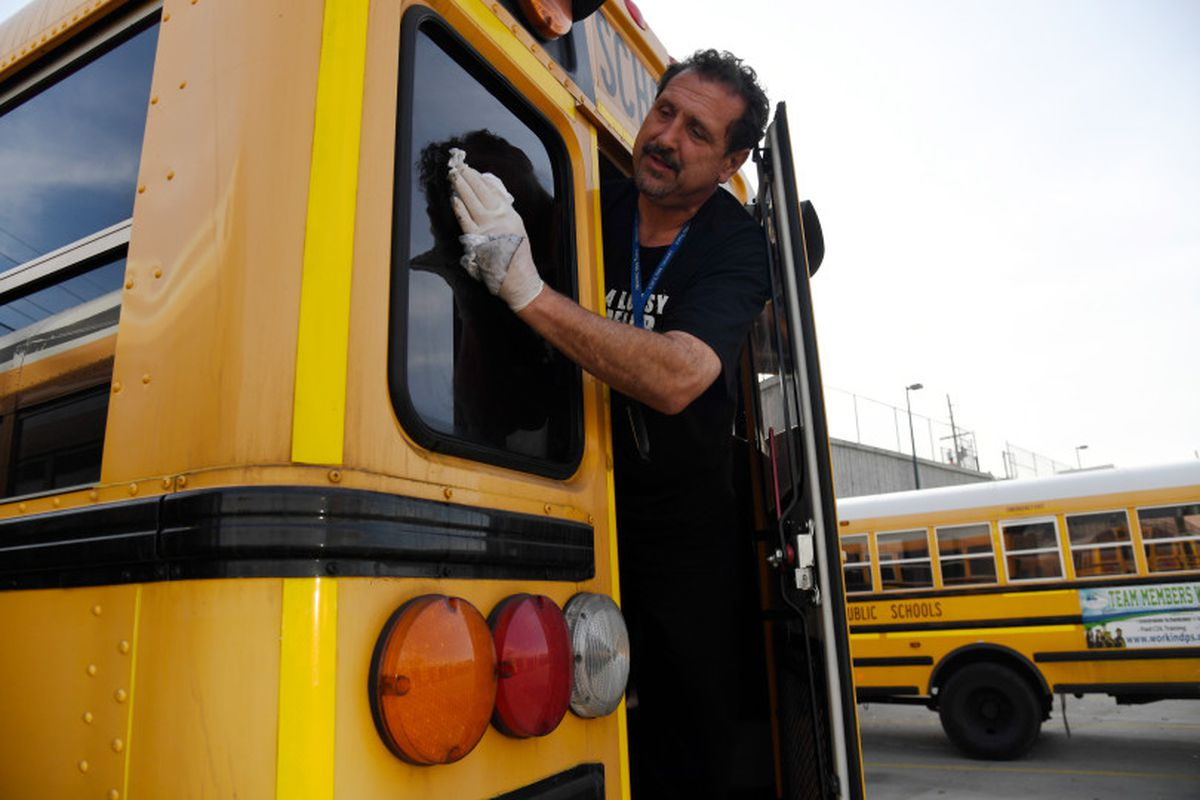 Paraprofessional Ben Johnson washes of the back window of a bus at the Denver Public Schools Hilltop Terminal November 10, 2017.