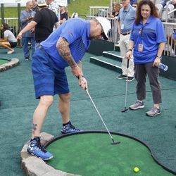 ESPN Radio host Rob Dibble putts in the mini golf tournament.