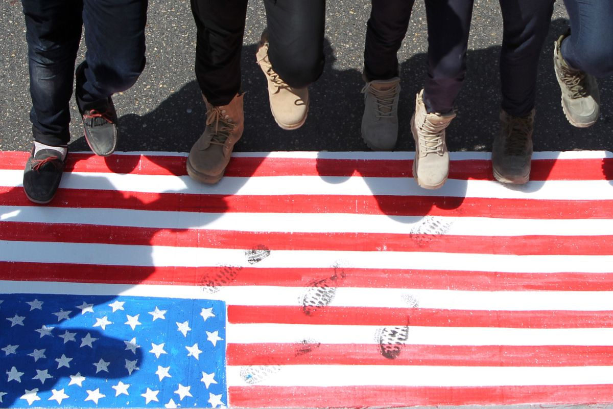 This is a picture of Iraqi men protesting because Getty Images doesn't have photos of Americans stepping on the flag.