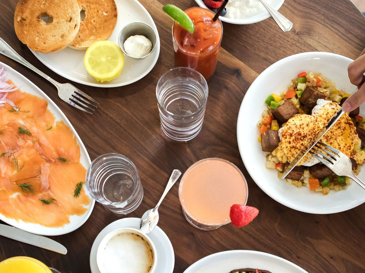 An overhead view of salmon, a bagel, and eggs Benedict