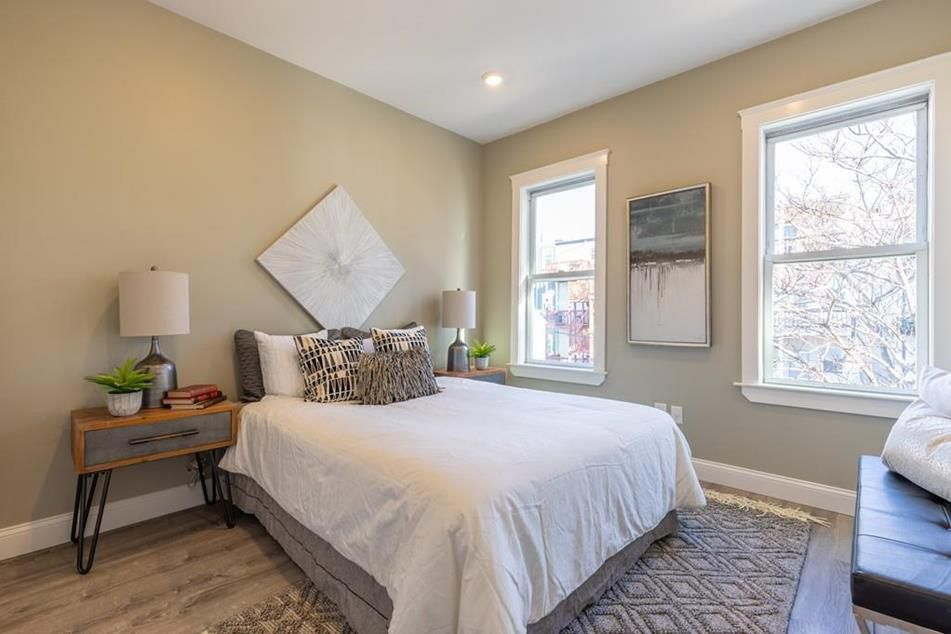 A bedroom with a bed and a nightstand and two windows.