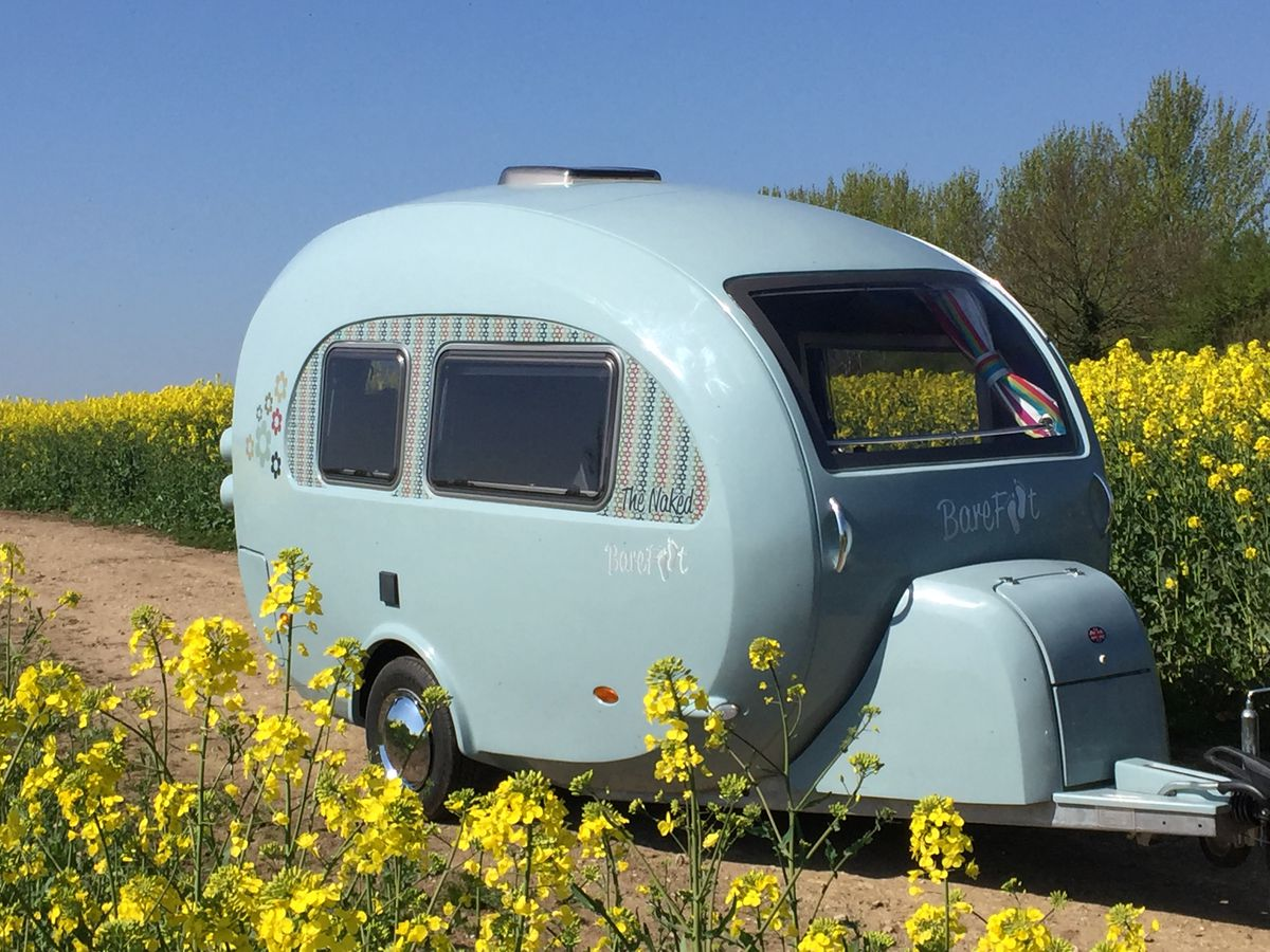 A light blue colored camper called the Barefoot Caravan. The camper is in a clearing in a field full of yellow wildflowers.