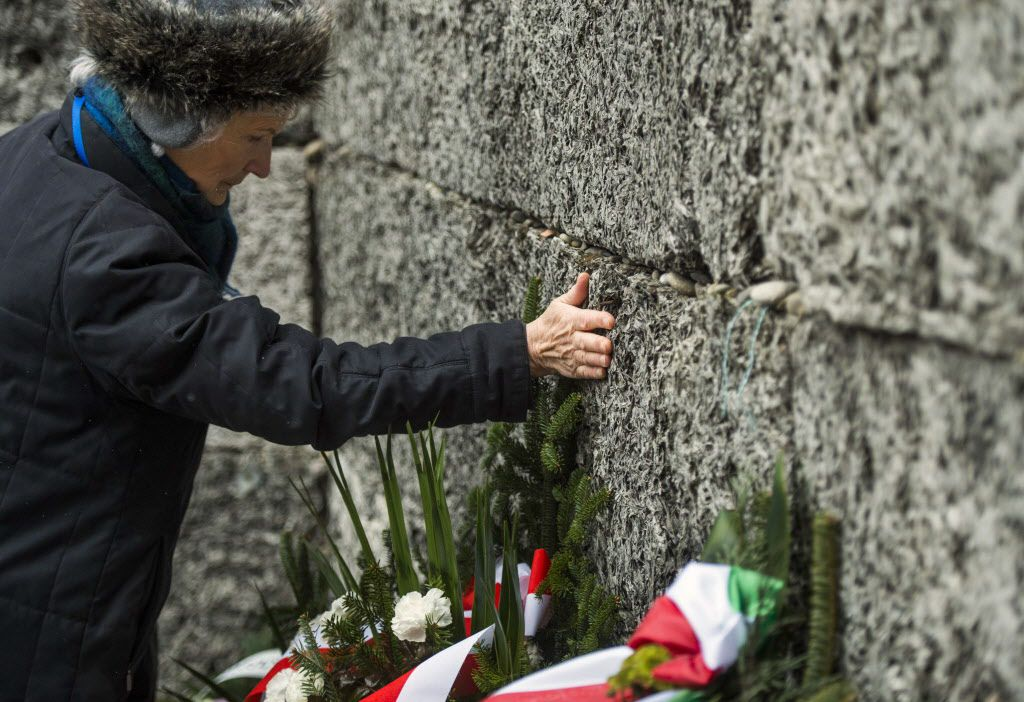 """<small><strong>A Holocaust survivor pays tribute to fallen comrades putting her hand on the """"death wall"""" execution spot in the former Auschwitz concentration camp in Oswiecim, Poland, on the 70th anniversary of the liberation of the Nazi death camp on Jan"""