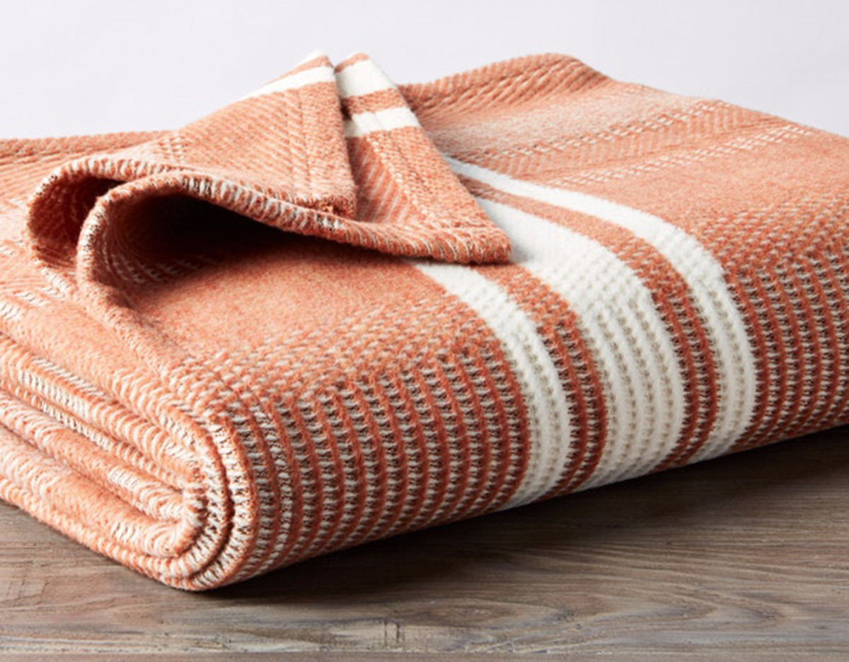 An orange and white patterned throw blanket which is folded neatly and sitting on a wooden surface.