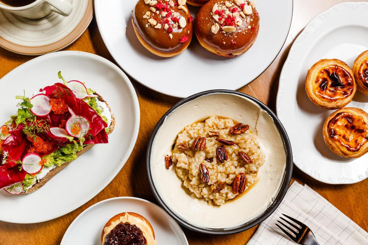 Atop a wooden table, a spread of five plates, including doughnuts, egg tarts, toast, and brown rice porridge.