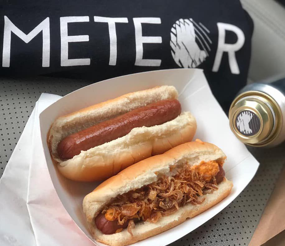 A plain dog and a kimchi and fried onion hot dog along with a can of tonic and a Meteor t-shirt