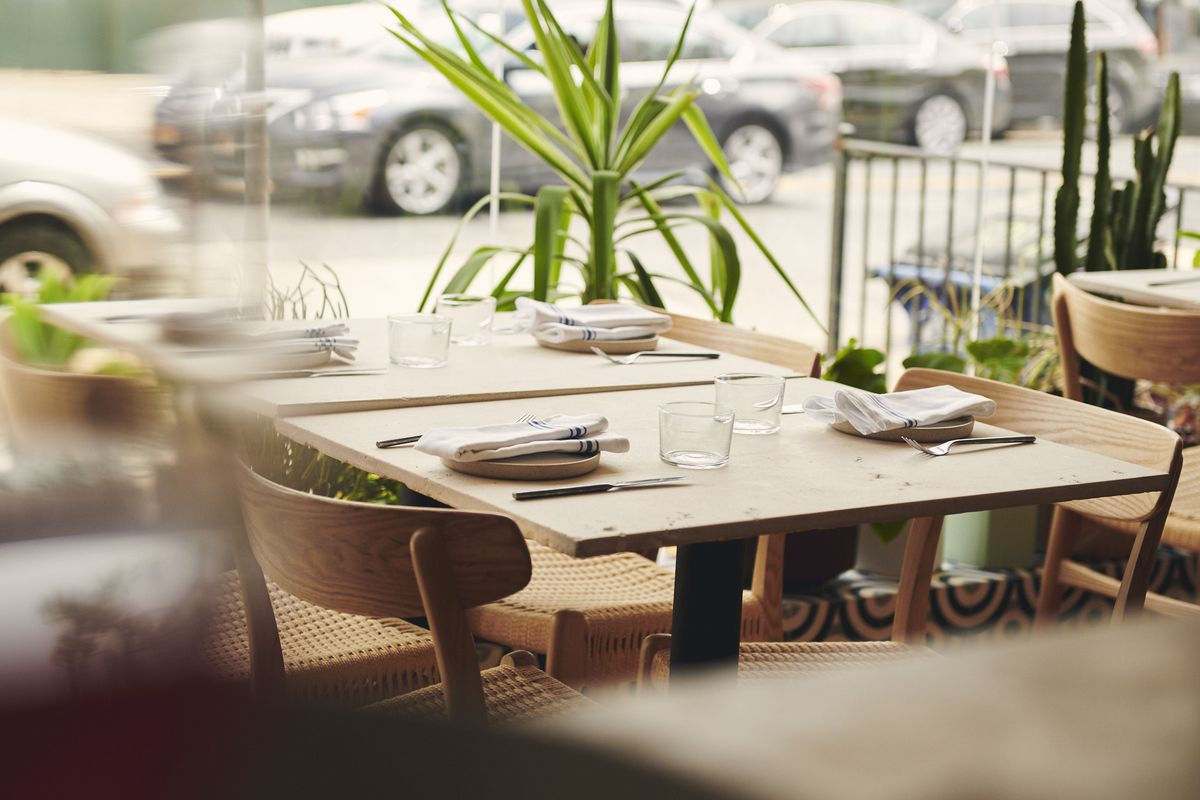 A close up photograph of a table set for service, with a window looking out on a street