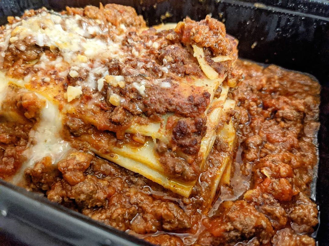 Closeup shot of a meaty Italian-style slice of lasagna, sitting in a black plastic takeout container