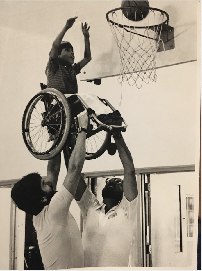 """Frank Burns (left), a fellow coach and one of their students.""""That epitomizes Frank, that he would lift a kid up so he could make a basket,"""" his brother said."""