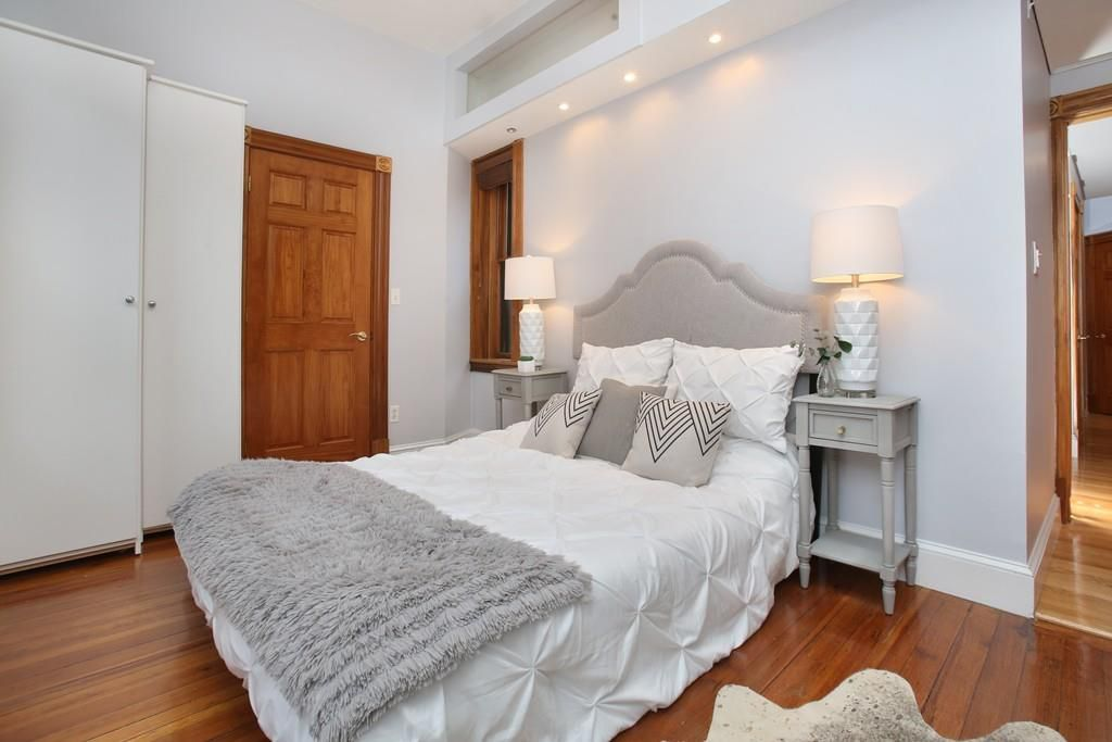 A bedroom with a bed and a closed closet door next to it.