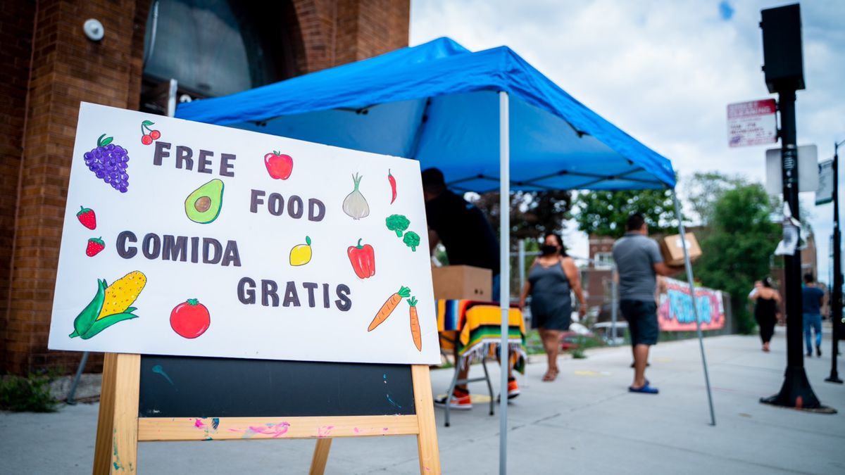 A sign with produce offerings on a sidewalk.