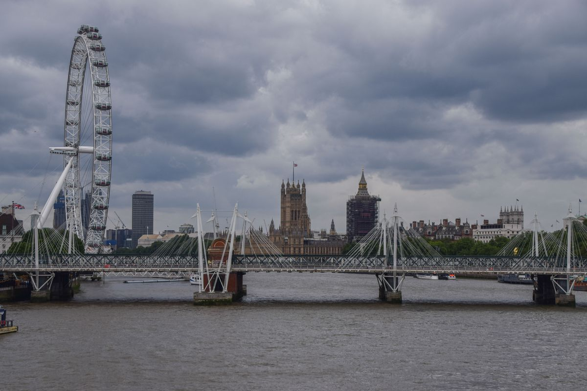 Dark clouds gather over the Houses of Parliament, London Eye...