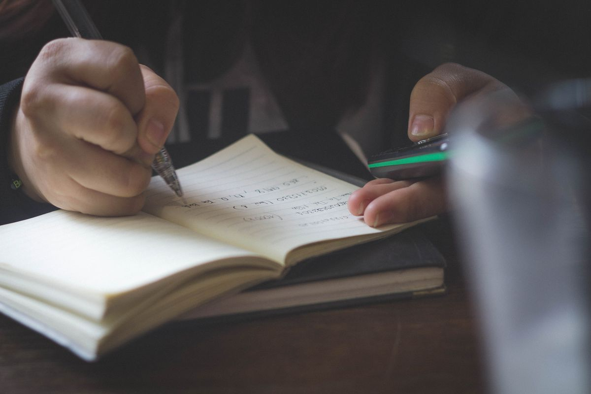 Close up of student writing in a notebook and looking at a phone.