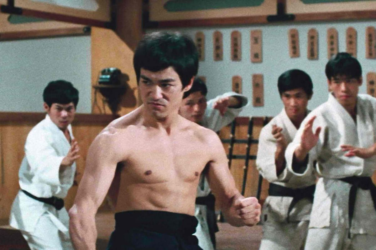 a shirtless Bruce Lee is ready for a fight in Fist of Fury