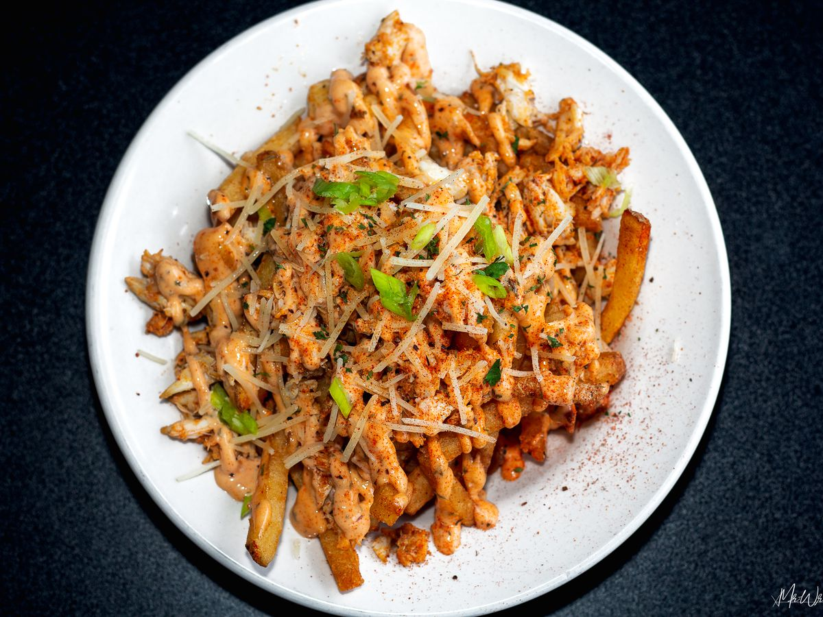 A plate of fries topped with bits of crab, herbs, and drizzles of sauce