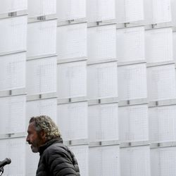 Artist Ned Kahn talks about his art installation, Pages of Salt, shown in the background, during its unveiling on Regent Street in Salt Lake City on Tuesday, Oct. 22, 2019. The installation is comprised of stainless steel rods and 336 Teflon flags that cover the entire north facade of the Walker Center parking garage. Kahn became fascinated with the site's connection to the printing presses of both the Salt Lake Tribune and Deseret News, which were located on Regent Street for over 80 years. The images of hundreds of newspaper pages draped on conveyer belts echo the many identical swaying parts Kahn often utilizes in his wind sculptures. The artwork is intended to suggest a vertical cloud of newspapers swaying in the wind. Managed by the Salt Lake City's Public Art Program and funded with $2.2 million from the Redevelopment Agency of Salt Lake City's major reconstruction of Regent Street, Pages of Salt is the city's largest investment in a single piece of public art to date.