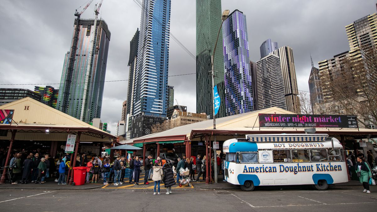 The American Doughnut Kitchen bus parks outside the Queen Victoria Market, beneath the Melbourne skyline