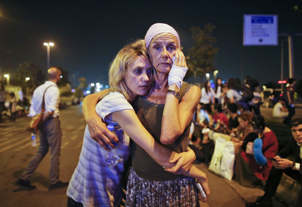 Passengers embrace as they wait outside Istanbul's Ataturk airport early Wednesday. | Emrah Gurel/AP