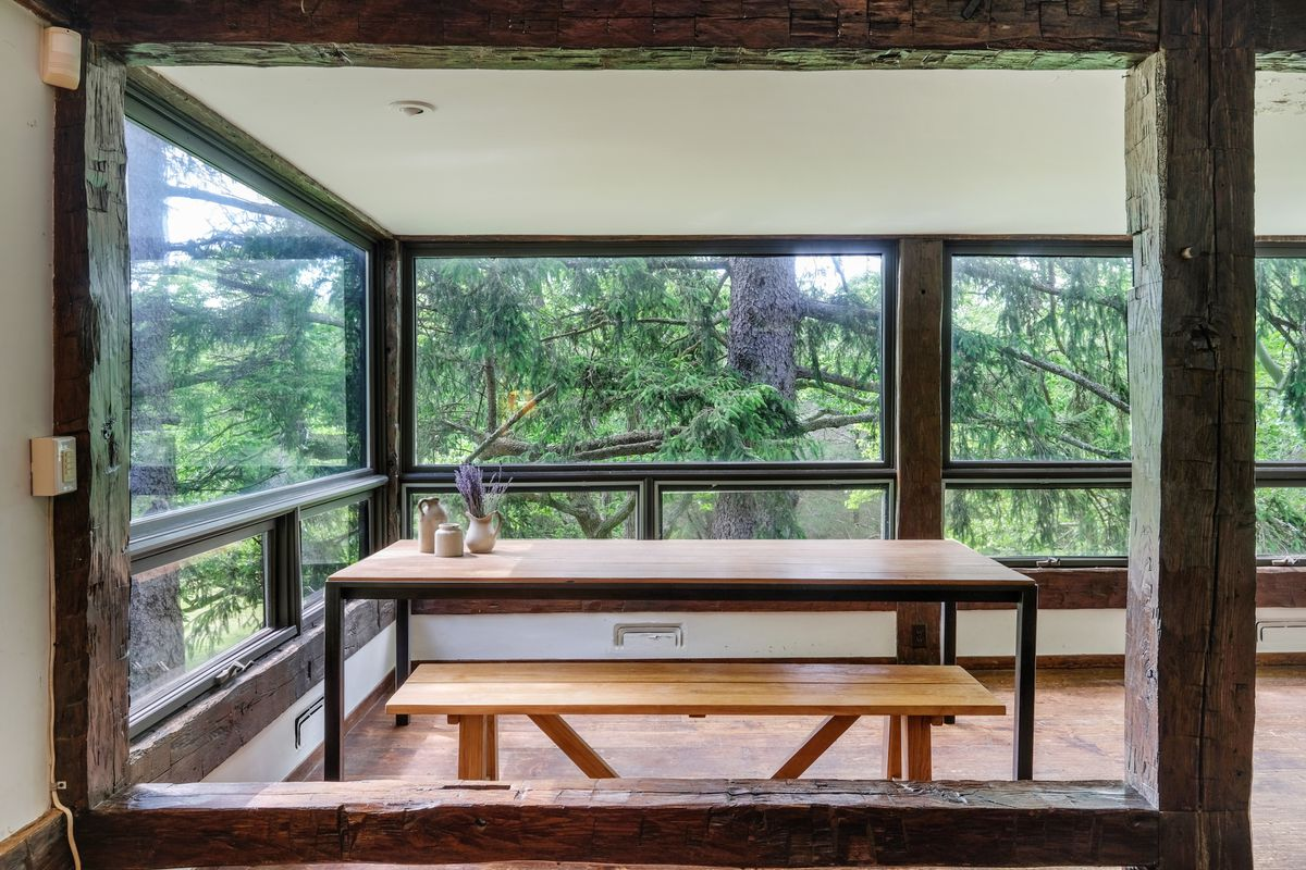 A wooden table with bench sits in a porch-like room with exposed beams and windows all around.