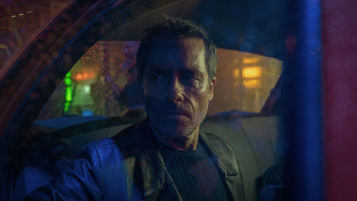 Guy Pearce scowls from a multicolored booth in Zone 414